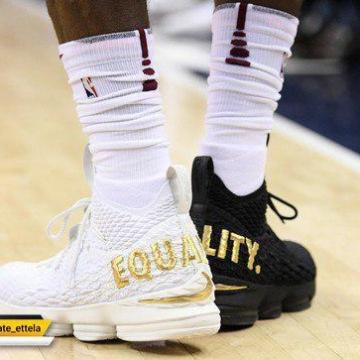 """کفش های سیاه و سپید که روی آنها عبارت """"برابری"""" به رنگ طلایی نقش بسته"""