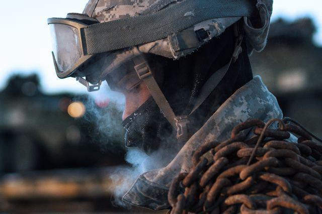 یک سرباز آمریکایی در حال جابهجایی بار سنگینی در سرمای زیر صفر درجه