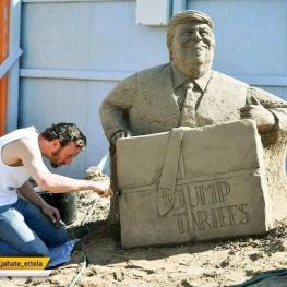 هنرمند بریتانیایی در حال کار روی مجسمه شنی دونالد ترامپ